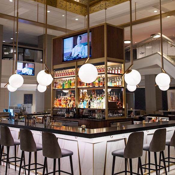 Bar seating overlooking wall of liquor and tvs